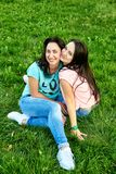 Two young happy girls lie on grass. Two young happy girls lie on green grass Royalty Free Stock Photo