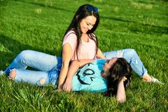 Two happy young girls lie on the grass Royalty Free Stock Images