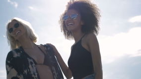 Two young happy hipster girls in sunglasses having fun, outdoor. Two pretty girlfriends smiling, laughing and fooling around during sunny day. Summer&friendship stock video