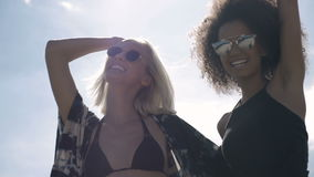 Two young happy hipster girls in sunglasses having fun, outdoor. Two pretty girlfriends smiling, laughing and fooling around during sunny day. Summer&friendship stock footage