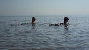 Two young  men lie in shallow water. handheld shooting. Two young happy men lie in shallow water. handheld shooting stock video footage