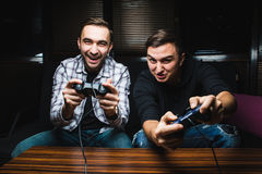 Two young happy men playing video games. While sitting on sofa Stock Photos