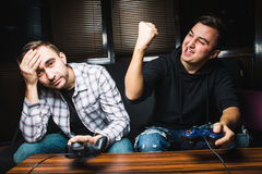 Two young happy men playing video games while sitting on sofa. Win and lose emotions Stock Photography