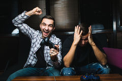 Two young happy men playing video games while sitting on sofa. Win and lose emotions Royalty Free Stock Photography
