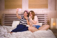 Two young happy and pretty Asian Chinese girlfriends sitting at home bedroom taking selfie portrait photo with mobile phone camera stock image