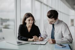 Two young happy smiling successful businesspeople working with document or contract at office. Success in business and teamwork co stock images