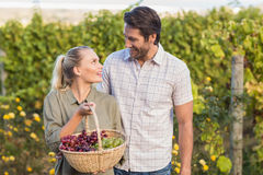 Two young happy vintners holding a basket of grapes Royalty Free Stock Photography