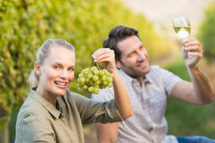 Two young happy vintners holding a glass of wine and grapes. In the grape fields Royalty Free Stock Images