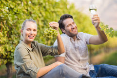 Two young happy vintners holding a glass of wine and grapes. In the grape fields Stock Images