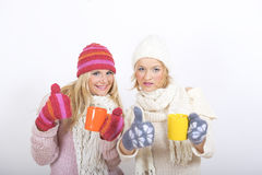Two young happy winter woman with cup of tea Stock Photos