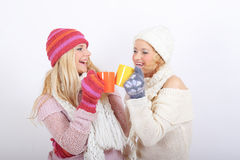Two young happy winter woman with cup of tea Royalty Free Stock Image