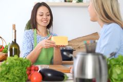 Two young happy woman making cooking in the kitchen. Friendship and culinary concept. Two young happy women making cooking in the kitchen. Friendship and Stock Photos