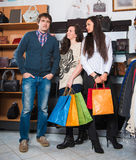 Two young happy woman with shopping bags and male  sales assista Royalty Free Stock Photo