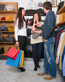 Two young happy woman with shopping bags and male sales assistan Stock Photography