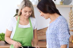 Two young happy women are cooking in the kitchen. Friends are having fun while preapering healthy and tasty meal Royalty Free Stock Photography