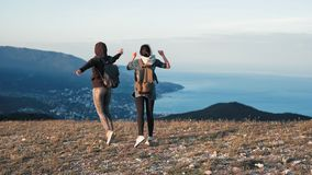 Two young happy women dancing and raising arms on beautiful mountain top over sunset sky.  stock video