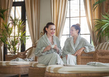 Two young happy women drinking tea at spa resort Royalty Free Stock Photography