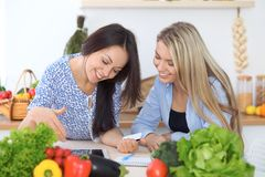 Two young happy women making online shopping for making menu by tablet computer. Friends cooking in the kitchen Stock Photos