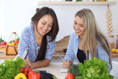 Two young happy women making online shopping for making menu by tablet computer. Friends cooking in the kitchen.  Stock Image