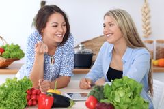 Two young  happy women are making online shopping by tablet computer and credit card. Friends are going to cook in th Stock Photography