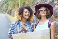 Two women planning route. Two young happy women on roadside holding a large map and planning their (walking)  route and stopping off points Royalty Free Stock Image