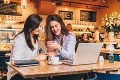 Two young happy women are sitting in cafe at table in front of laptop, using smartphone and laughing.