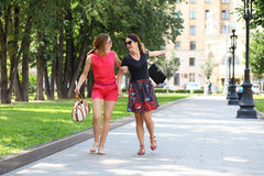Two young happy women walking in the summer city Stock Image