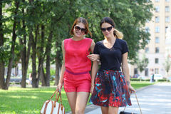 Two young happy women walking in the summer city Royalty Free Stock Images