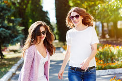 Two young happy women walking in the summer city Stock Images