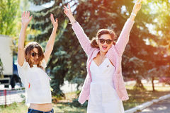 Two young happy women walking in the summer city Royalty Free Stock Image