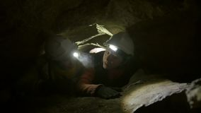 Two young hikers explorers stuck in the narrow hole in dark cave. Close up stock video footage