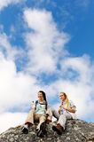 Two young hikers in the great outdoors. Two women take a break from trekking and rest on a rock outdoors stock photos