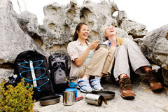 Two young hikers relaxing after a tough day hiking. Two friends enjoy a laugh together while camping outdoors after a hike in the wilderness royalty free stock image