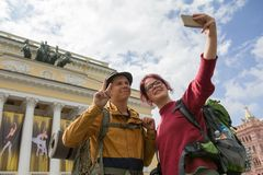 Two young hikers taking selfies in front of a historic building. Telephoto shot Stock Photography