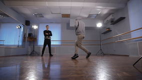 Two young hip-hop dancers participating in dance battle. Teenager in black trousers and pullover watching his friend stock footage