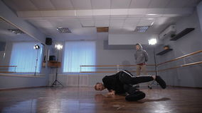 Two young hip-hop dancers participating in dance battle. Young man in grey pullover and trousers watching his friend. Two young hip-hop dancers are participating stock video