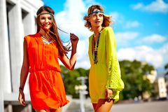 Two young hippie women models in bright colorful hipster clothes Stock Photography