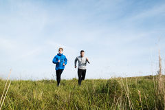 Two young hipster athletes running in sunny autumn nature Royalty Free Stock Photo