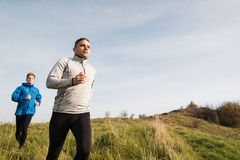 Two young hipster athletes running in sunny autumn nature Royalty Free Stock Images