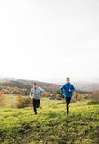Two young hipster athletes running in sunny autumn nature Stock Photography