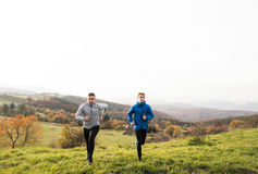 Two young hipster athletes running in sunny autumn nature Royalty Free Stock Photos