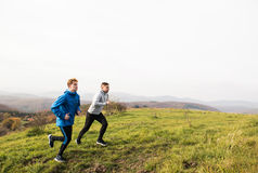 Two young hipster athletes running in sunny autumn nature Stock Photo