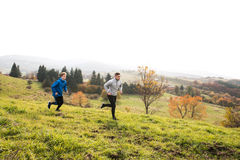 Two young hipster athletes running in sunny autumn nature Stock Photos