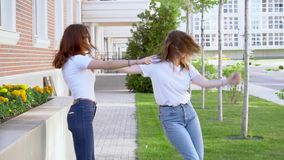 Two young hipster girl friends dancing outdoor slow motion stock footage