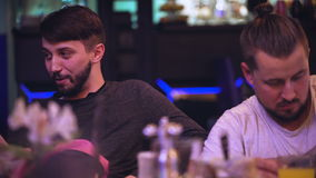 Two young hipster in a nightclub. Men sitting at the table and talk to their friends, associates stock video