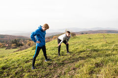 Two young hipster runners in sunny autumn nature restinng Royalty Free Stock Image