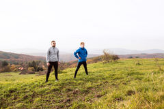 Two young hipster runners in sunny autumn nature restinng Stock Photos