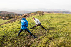 Two young hipster runners in sunny autumn nature stretching legs Stock Photos