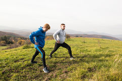 Two young hipster runners in sunny autumn nature stretching legs Stock Photography