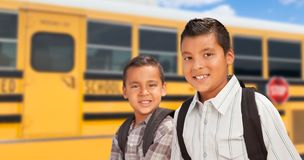 Two Young Hispanic Boys Walking Near School Bus stock photo
